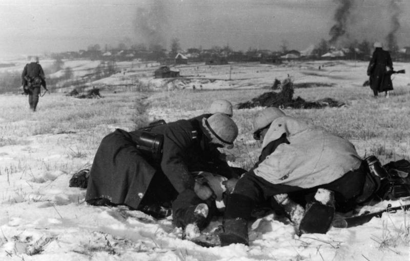 Немецкие солдаты во время атаки под Москвой оказывают помощь раненому.