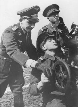 Немецкий инструктор обучает румынского солдата работе на зенитном орудии. Апрель 1941 г.