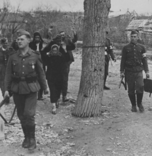 Немецкие солдаты конвоируют задержанных советских граждан на окраине Новороссийска. 1942 г.
