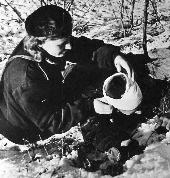 Военфельдшер перевязывает раненого красноармейца, во время боев на «Малой земле». Февраль 1943 г.