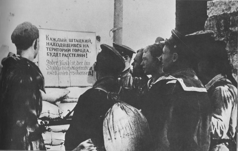 Краснофлотцы возле немецкого объявления в освобожденном Новороссийске. Октябрь 1943 г.