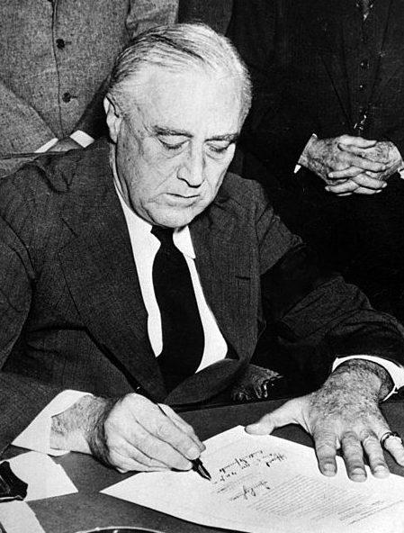 Президент Рузвельт, с траурной повязкой на рукаве, подписывает Декларацию о войне с Японией.