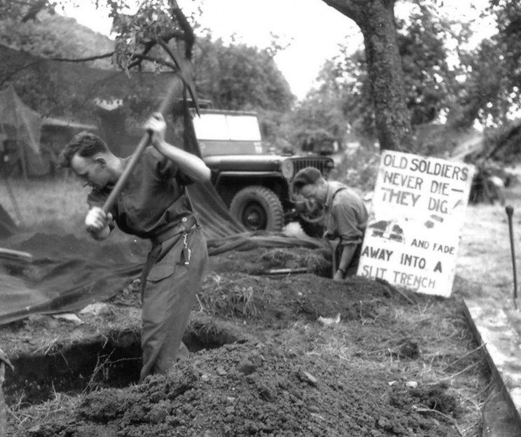 Канадцы роют оборонительные окопы и щели в Нормандии. На щите написано: «Старые солдаты никогда не умирают — они роют окопы и исчезают в щелях». 25 июня 1944 г.