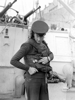 Моряк торпедного катера Канадского флота демонстрирует пулевое отверстие в жилете. Кан, июнь 1944 г.