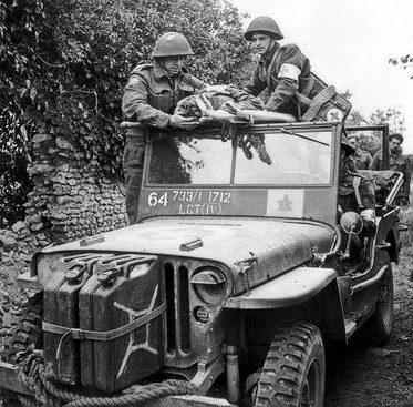 Канадские медики эвакуируют раненого солдата из канадской 3-й пехотной дивизии. Франция, июнь 1944 г.