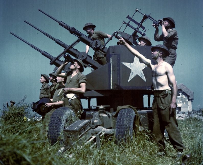 Канадские артиллеристы у трехствольной установки «Польстен» на нормандском пляже Джуно. Июнь 1944 г.