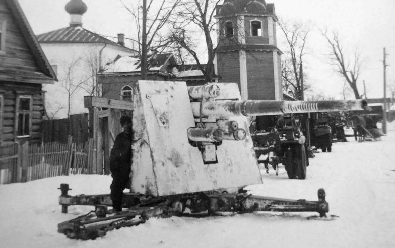 Солдат Вермахта возле 88-мм зенитного орудия, установленного на дороге в Демянске. Февраль 1942 г.
