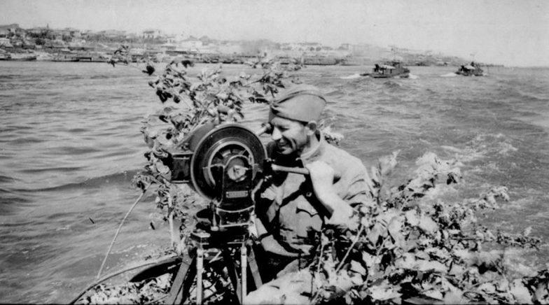 Кинооператор Валентин Орлянкин снимает с борта катера панораму Сталинграда. 1942 г.
