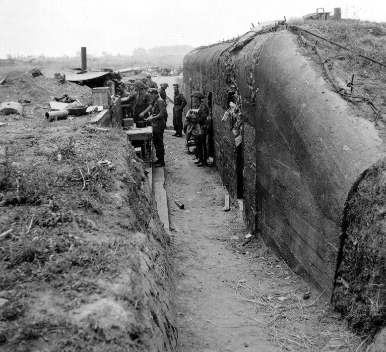 Солдаты 3-й канадской пехотной дивизии у немецкого бункера на аэродроме деревни Карпике. 12 июля 1944 г.