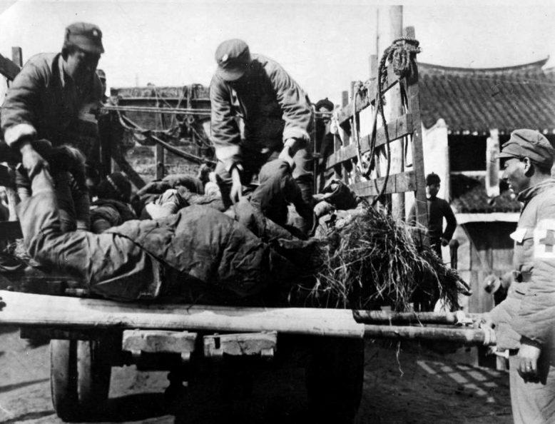 Китайские санитары грузят тела убитых на улице Шанхая. 1937 г.