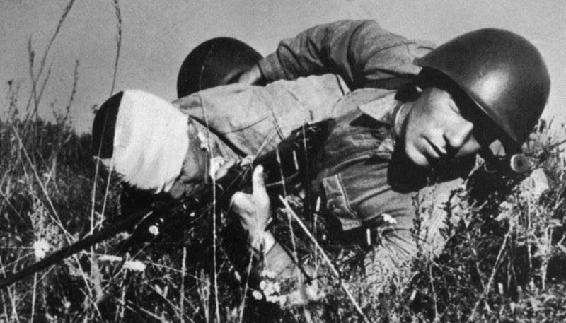 Красноармеец вытаскивает раненого с поля боя на подступах к Сталинграду. Июль 1942 г.