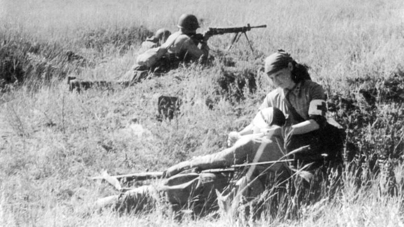 Медсестра на поле боя оказывает помощь раненому бойцу. Июль 1942 г.