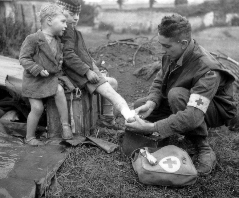 Канадский медик перевязывает ногу французскому мальчику. Июль 1944 г.