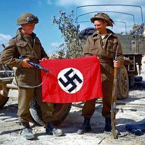Канадские солдаты с нацистским флагом захваченным в битве к юго-востоку от Кана. 10 августа 1944 г.