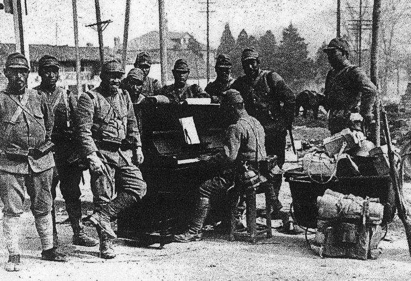 Японский солдат играет на пианино посреди улицы Чжуншань в Нанкине. 1937 г.
