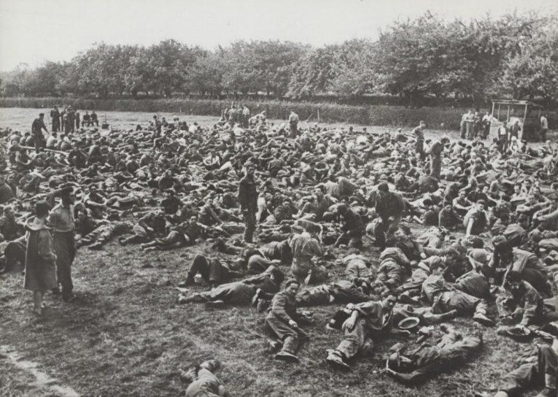 Канадские военнопленные ждут транспорта под охраной немцев после битвы при Дьеппе. Август, 1942 г.