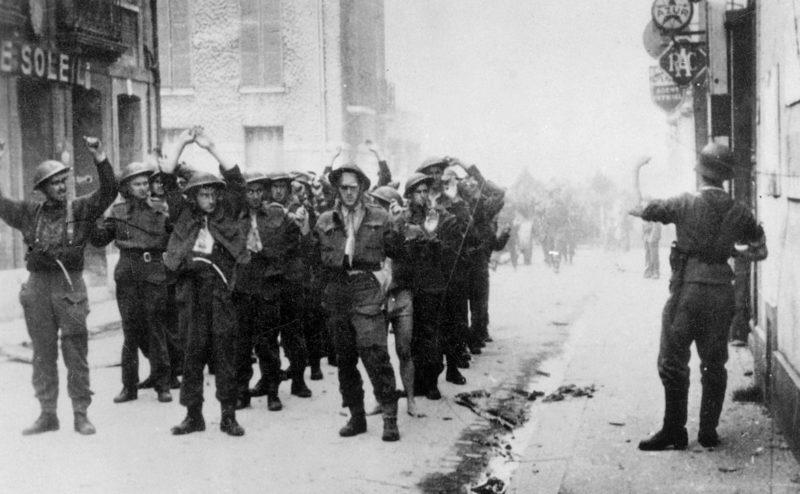 Немецкие солдаты отправляют группу канадских солдат в лагерь после битвы при Дьеппе. Август, 1942 г.