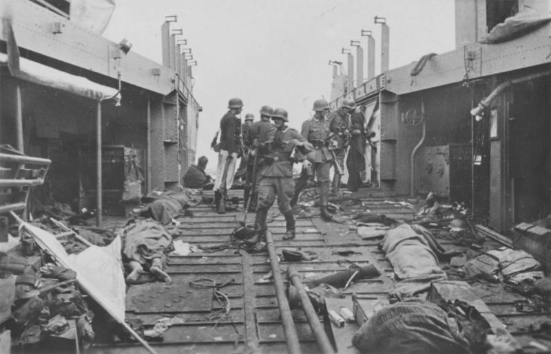 Немецкие солдаты осматривают десантный катер с телами убитых канадских и британских солдат в Дьеппе. Август 1942 г.