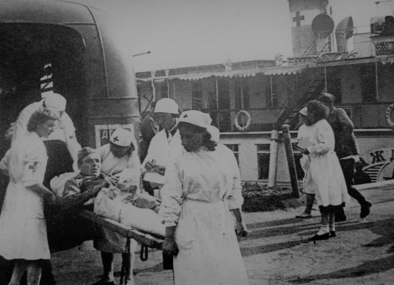Переноска раненого красноармейца на носилках на берегу Волги к санитарному пароходу «Гражданин». 1942 г.