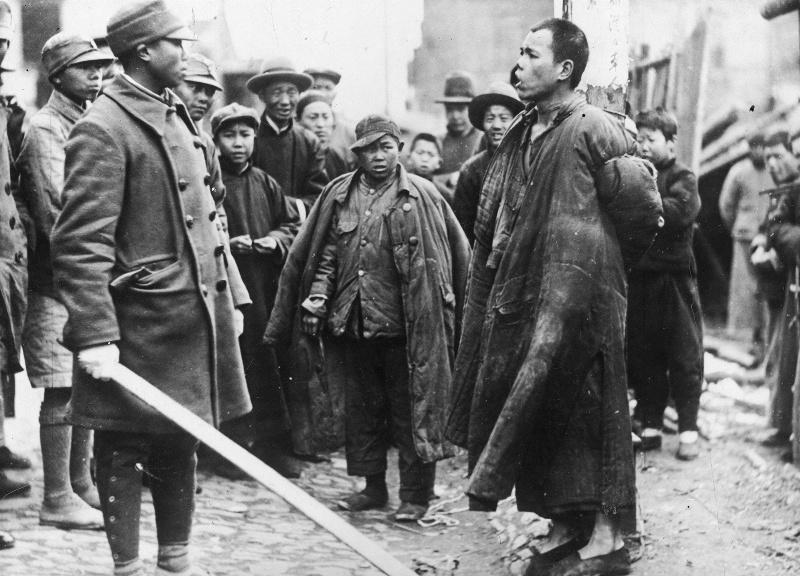 Офицер армии Гоминьдана допрашивает китайца, обвиненного в шпионаже в пользу японцев. 1938 г.