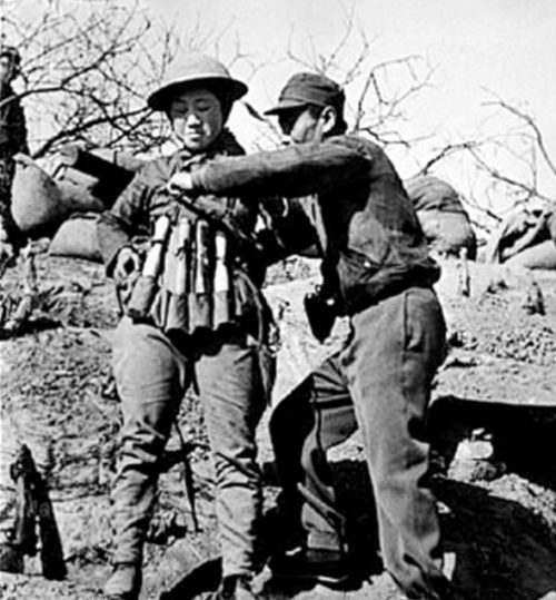 Китайский террорист-смертник надевает взрывной жилет, изготовленный из ручных гранат, для использования при нападении на японские танки в битве при Тайержуане. 1938 г.