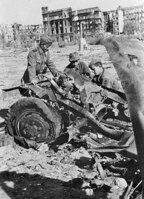 Военнопленный помогает солдатам Вермахта разбирать разбитый советский автомобиль в Сталинграде на площади Павших Борцов. Октябрь 1942 г.