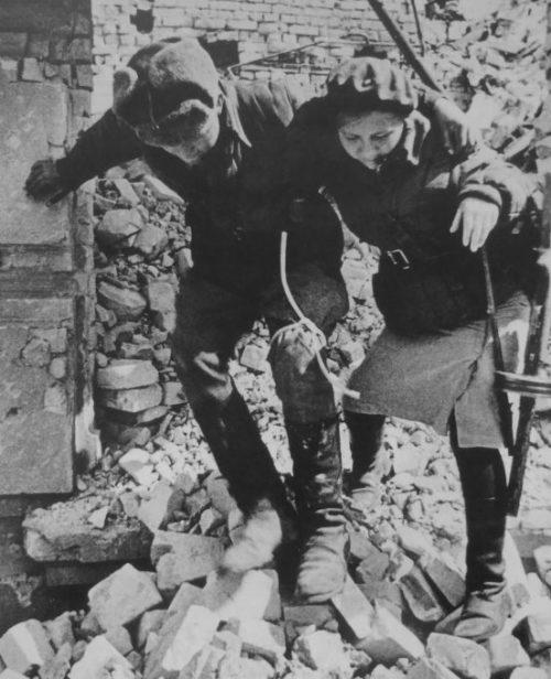 Девушка-санинструктор сопровождает раненого солдата. Октябрь 1942 г.