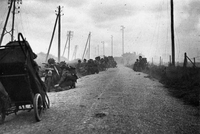 Канадские солдаты укрываются от огня на дороге у пляжа Юнона. 6 июня 1944 г.