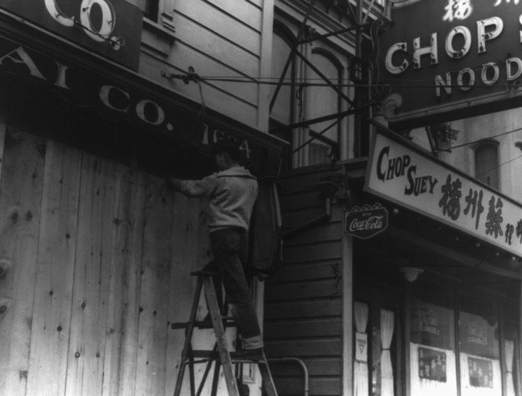 Японец забивает двери своего магазина перед отправкой в лагерь для интернированных.