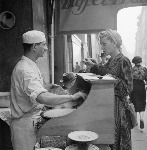 Парижанка завтракает в блинной на улице города. Май 1941 г.
