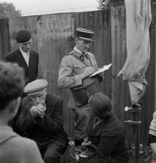 Полицейский выписывает штраф продавцу на блошином рынке в оккупированном Париже. Май 1941 г.