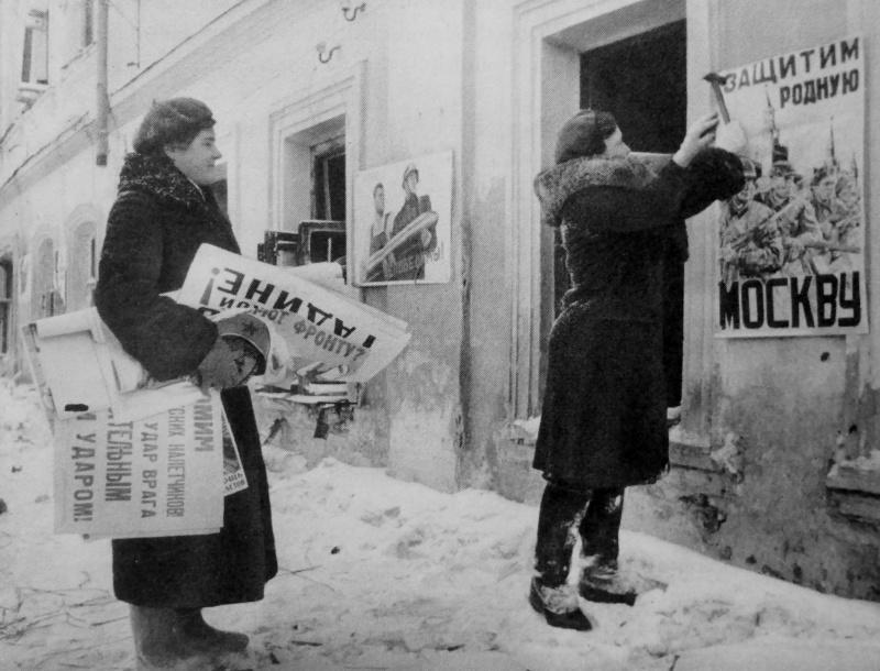 Девушки прибивают агитплакаты на улице освобожденного Можайска. Январь 1942 г.