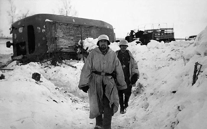 Немецкие солдаты на фоне разбитой штабной колонны. Март 1942 г.