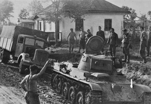 Венгерский танк 38M Toldi I вытаскивает немецкий грузовик в советской деревне. 1941 г.