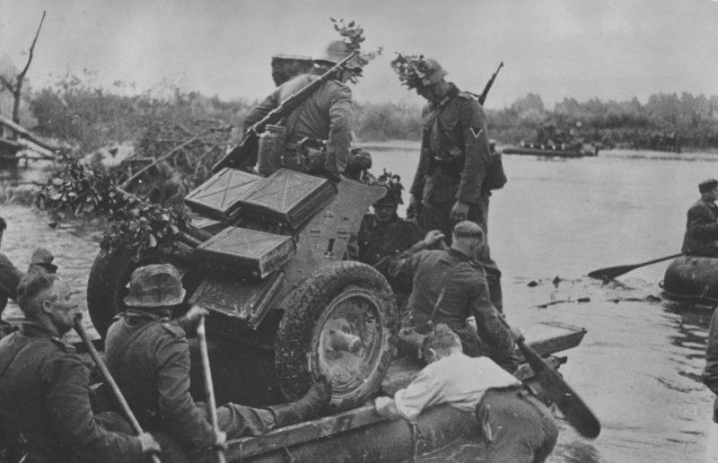 Немецкие артиллеристы переправляют противотанковую пушку на лодке через Маас. Май 1940 г.