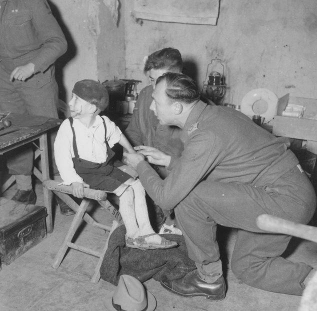 Британский медик оказывает помощь итальянскому мальчику, пострадавшему в результате немецкого артобстрела. Январь 1944 г.