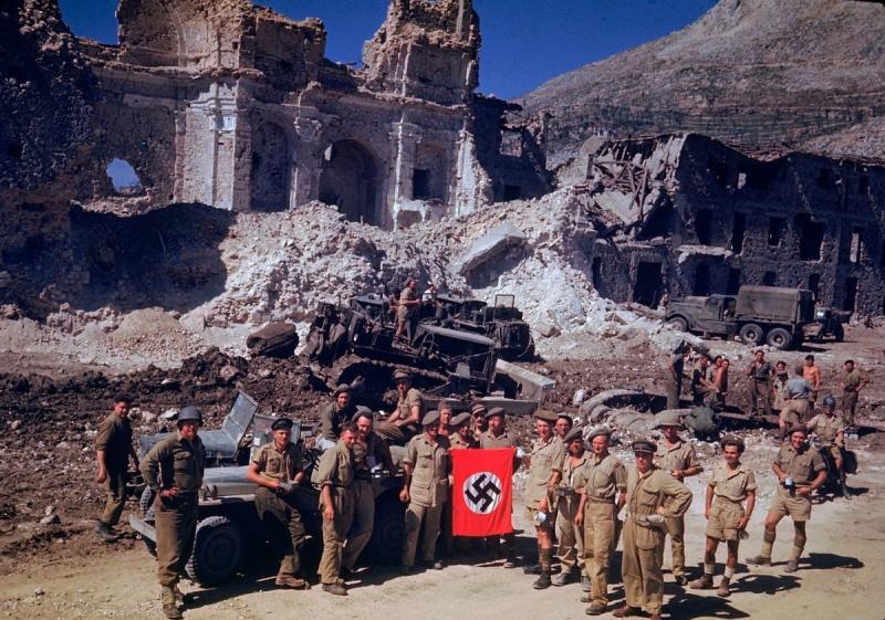 Солдаты союзников с захваченным нацистским флагом на руинах города в Италии. 1944 г.