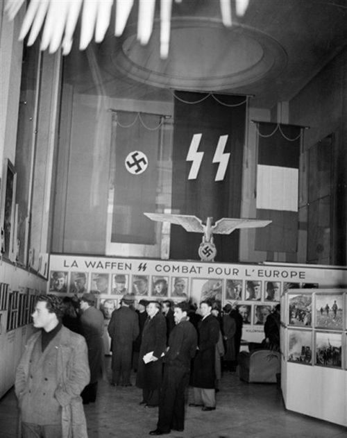 Посетители фотовыставки «Войска СС» в выставочном зале фирмы «Ситроен» в Париже. Февраль 1944 г.