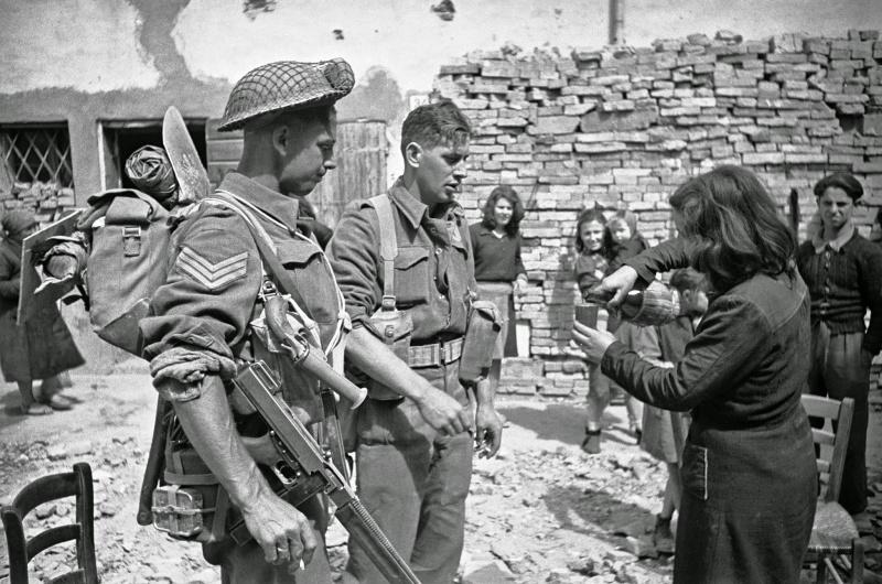 Итальянская женщина угощает вином новозеландских пехотинцев в Барбьяно. Апрель 1945 г.