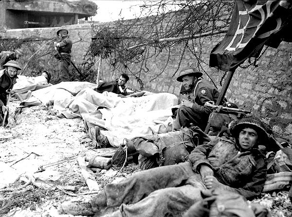 Раненые канадские солдаты ожидают эвакуации на пляже Юнона. 6 июня 1944 г.