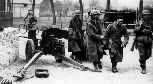 Пленные французские солдаты несут раненого товарища в бельгийский город. 1940 г.