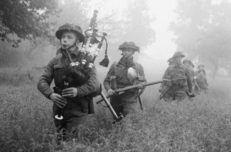 Волынщик 7-го полка горцев Сифорта возглавляет колонну наступающих в районе города Кан. 26 июня 1944 г.