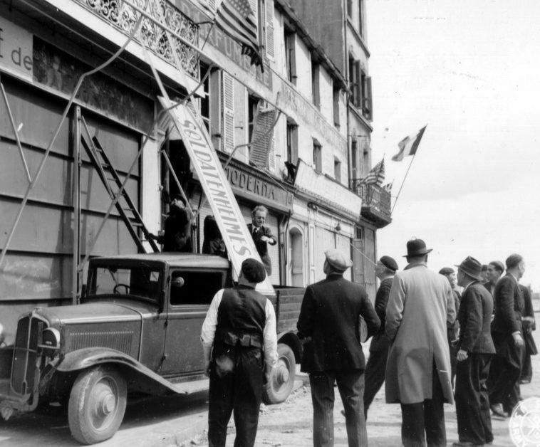 Французы снимают немецкую вывеску с фасада здания в Шербуре. 28 июня 1944 г.