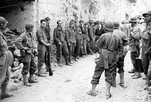 Солдаты французского экспедиционного корпуса охраняют немецких военнопленных на улице итальянского городка. Июль 1944 г.