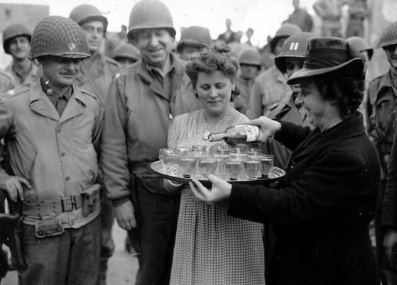 Француженки угощают американских офицеров вином на площади в Тревьере. 14 июля 1944 г.