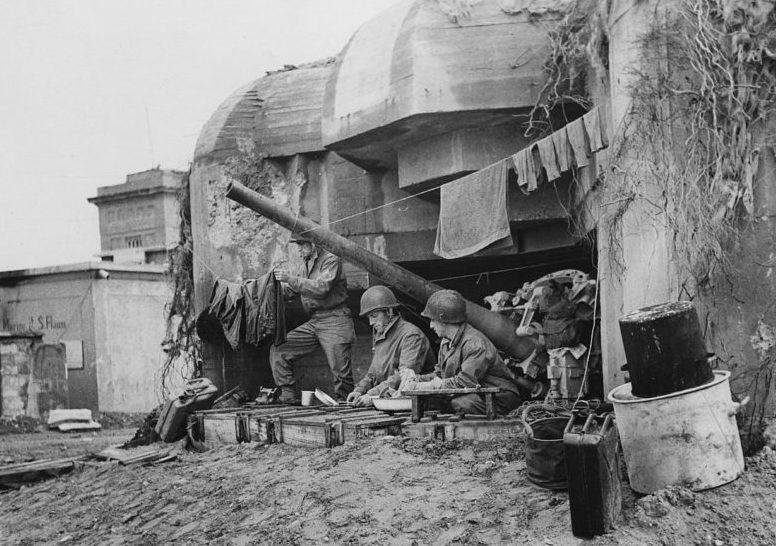 Американские солдаты у захваченного бункера берегового орудия. 10 июля 1944 г.