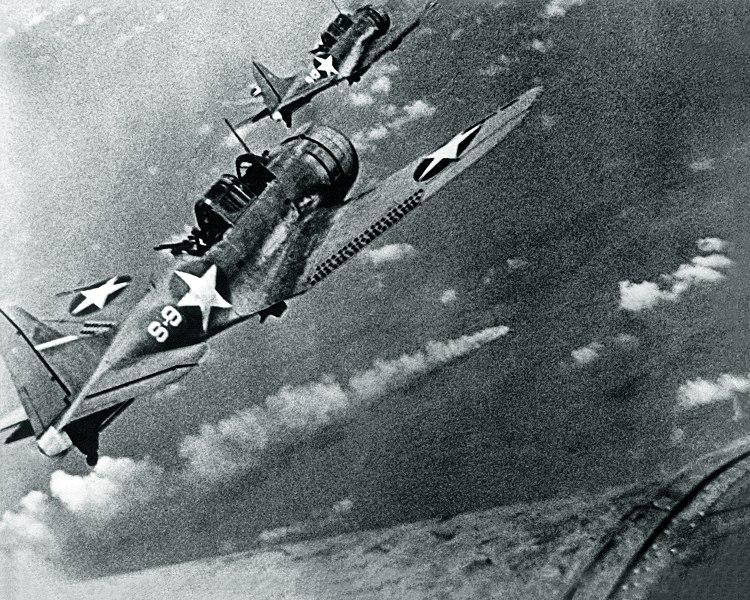 Американские пикировщики заходят в атаку на горящий крейсер «Микума».