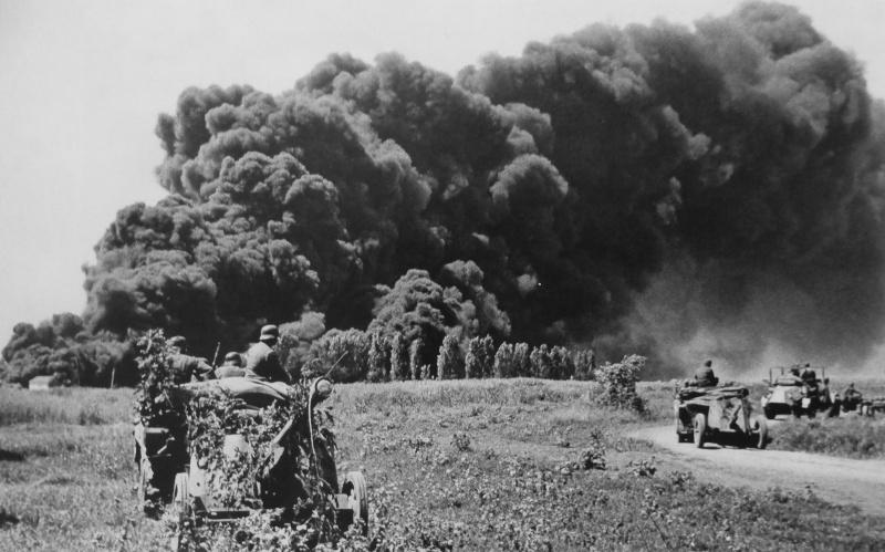 Немецкие солдаты на фоне дыма от горящих нефтяных скважин Майкопа, подожженных при отступлении советских войск. Август 1942 г.