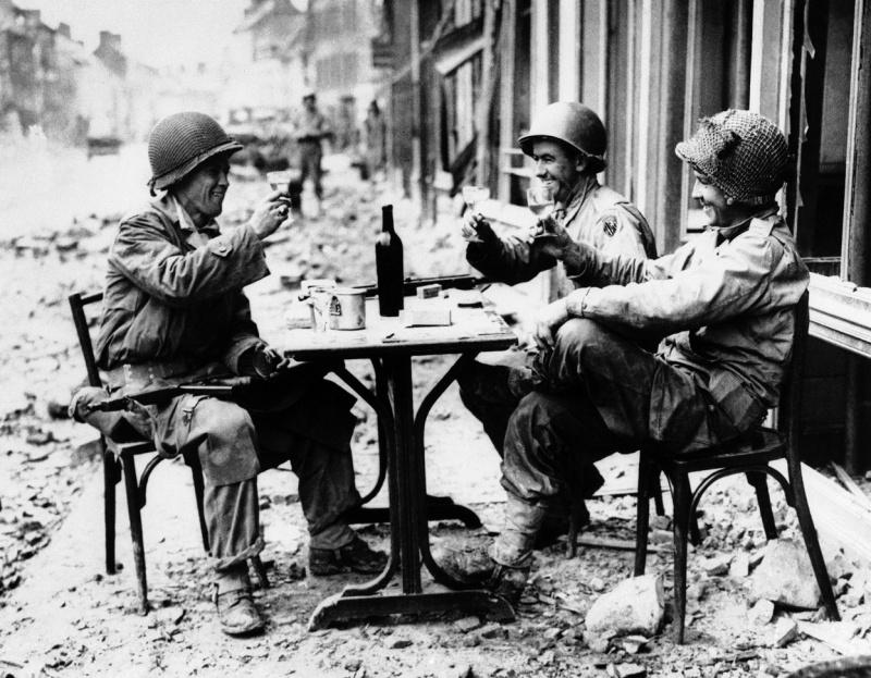 Американские военные изображают уличное кафе на улице городка Ла Э-дю-Пюи. 15 июля 1944 г.