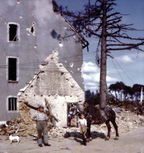 Французский фермер с сыном у дома, разрушенного при бомбардировке союзниками. Июль 1944 г.